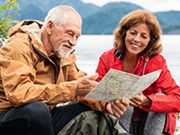An older couple reading a map, near a lake