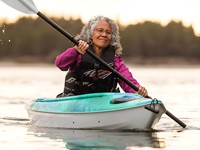 Older woman kayaking alone
