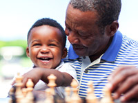 Grandfather teaching grandson chess