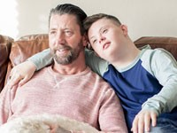 Father, son and dog watching TV on a couch